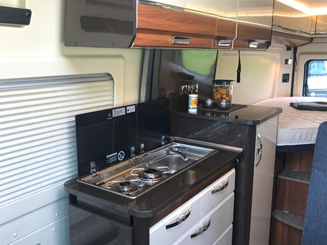 La cocina del camper Vantana 65, al fondo la cama